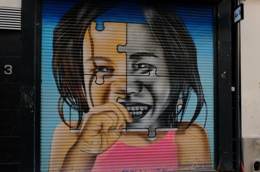 A window is covered by venetian blinds. The closed blinds create an image of a young child with an open-mouthed smile, raising their loosely closed right hand to their mouth. The child's face is stylized to resemble four pieces of a jigsaw puzzle, with the left half in color and the right half in black and white. The symbolism is that people are like puzzle pieces, their rigidity allowing them to only connect with certain other pieces but not others. Through personal growth, we can become more flexible, allowing us to forge the kinds of relationships needed to bring about social change.