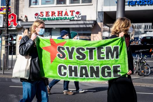 """Two people are walking while carrying a banner that says """"system change."""" The personal is political means that without individuals being willing to change their behavior, systemic change is not possible."""