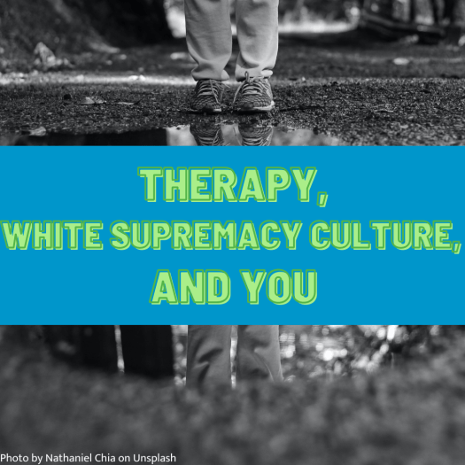 """A person is standing facing the camera at the edge of a puddle of water on the ground. Only their legs and feet are visible, and their image is reflected in the puddle. The image includes the words """"Therapy, white supremacy culture, and you."""""""