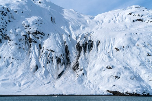 One of Fairweather's ant-sized survey launches against the snowy and mountainous College Fiord walls.