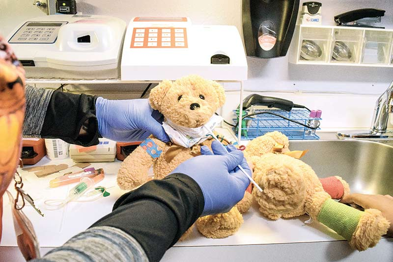 Teddy bear getting poked and prodded.