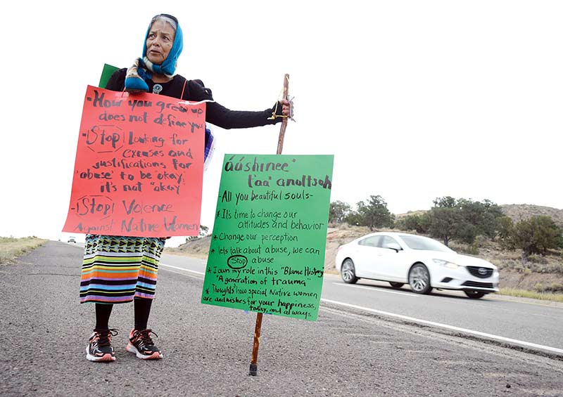Woman in tennis shoes on roadside with two large signs, as car passes by her.