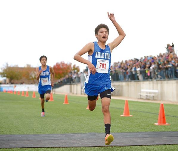 Runner raises left index finger as he crosses finish line.