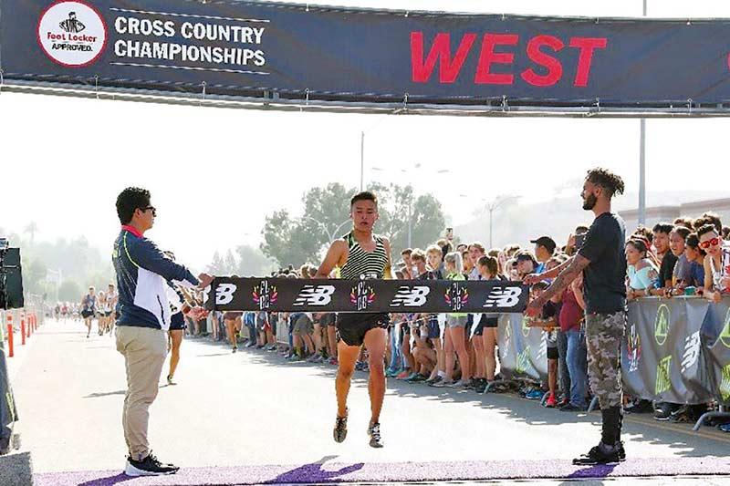 Runner prepares to race through finish line banner