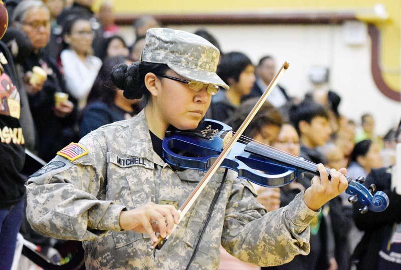 girl in military uniform plays blue violin