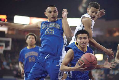 Navajo Times | Donovan Quintero Fort Thomas Apache Skylar Kindelay holds onto the ball as teammate Kobe Talgo (23) and a Gregory School defender leap into the air behind him Saturday in Prescott Valley, Ariz.