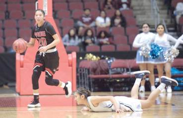 Navajo Times | Donovan Quintero Lady Sand Devil Myka Taliman (20) takes the ball by fallen Window Rock Lady Scout Rayel Holyan Friday at the Gila River Arena.