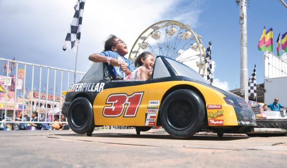 Navajo Times | Ravonelle Yazzie Kemara Nichols, 6, rides the racecar with a classmate during Kids' Day at the Navajo Nation Fair in Window Rock.