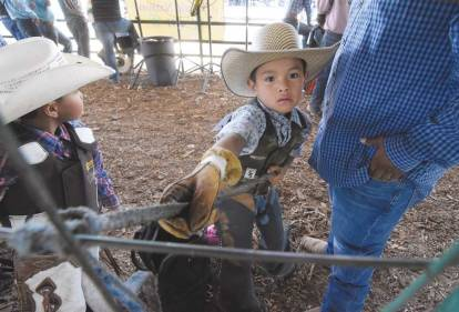 Navajo Times | Ravonelle Yazzie Five-year-old Tyrese Smith of Pine Hill, N.M., applies rosin onto his rope before the start of the wooly riding competition during the Navajo Nation Fair on Sept. 7.
