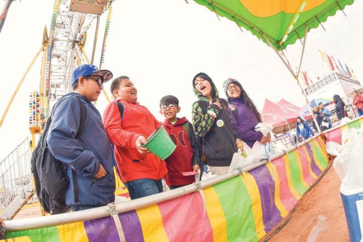 Navajo Times | Krista Allen The friends of Levi Black (in red), 11, cheer him on as he tosses balls into fish bowls in an attempt to win a goldfish during a rainy Kids Day at the 50th annual Western Navajo Fair on Oct. 11.
