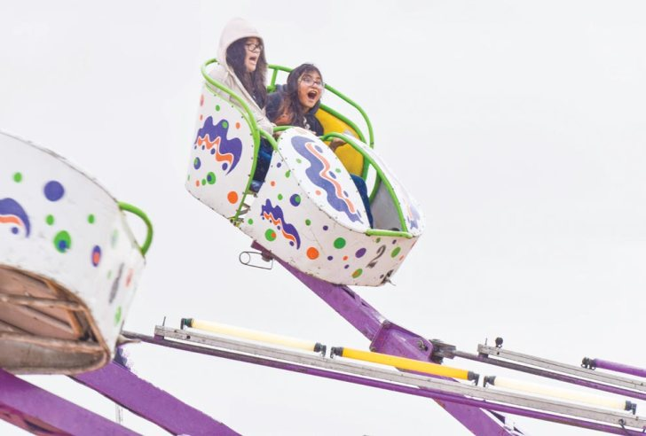 "Navajo Times | Krista Allen Two girls enjoy the ""Octopus"" ride during a rainy Kids Day at the 50th annual Western Navajo Fair on Oct. 11."