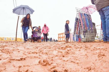 Navajo Times | Krista Allen Fairgoers walk through mud at the fairground during a rainy Kids Day at the 50th annual Western Navajo Fair on Oct. 11.