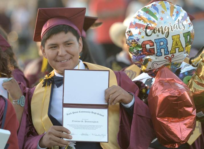 Navajo Times | Donovan Quintero Rock Point High graduate Eronimo S. Hummingbird holds his diploma during his graduation on Saturday evening in Rock Point, Ariz.