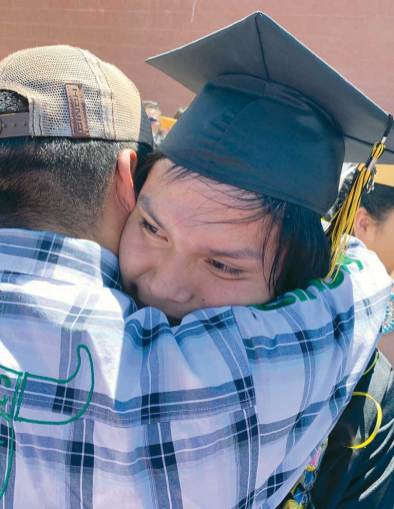Navajo Times | Cindy Yurth Chinle High School grad Matthew Nez gets a proud bear hug from his father, Vernon Nez, after Saturday's commencement in the Wildcat Den. Matthew plans to attend Diné College.