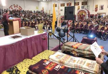 "Navajo Times | Donovan Quintero Guest speaker Buu Van Nygren, left, a candidate for vice president in last year's election, begins his speech at the To""Hajiilee High graduation on Saturday."