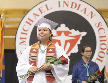 Navajo Times | Donovan Quintero St. Michael High graduate Deana Wilson looks for her family as she walks off the stage with some roses that she'll give them during her graduation in Fort Defiance on Saturday.