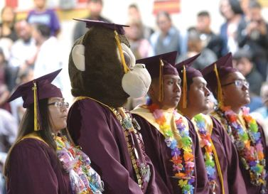 Navajo Times | Donovan Quintero To'Hajiilee High graduate Austin Long looks on while wearing a monkey mask on Saturday morning during his graduation in To'Hajiilee, N.M.