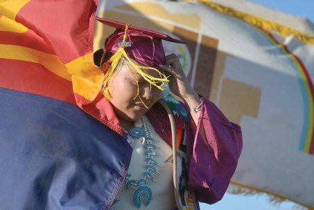 Navajo Times | Donovan Quintero A Rock Point High graduate walks off the stage as the Navajo Nation flag blows in the wind on Saturday in Rock Point.
