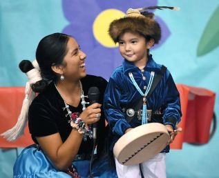 Navajo Times   Ravonelle Yazzie Jaiden Willeto helps her son Malakai Money, 3, on stage during the baby contest on Sept. 4 during the Navajo Nation Fair.