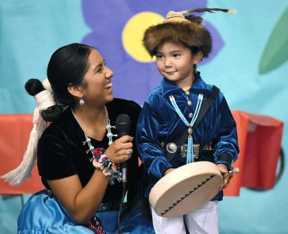Navajo Times | Ravonelle Yazzie Jaiden Willeto helps her son Malakai Money, 3, on stage during the baby contest on Sept. 4 during the Navajo Nation Fair.
