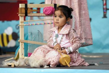 Navajo Times   Ravonelle Yazzie Three-year-old Melissa Wooten demonstrates how to use a spindle to spin wool during the baby contest on Sept. 4 during the Navajo Nation Fair in Window Rock.