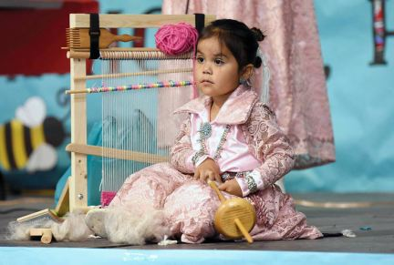Navajo Times | Ravonelle Yazzie Three-year-old Melissa Wooten demonstrates how to use a spindle to spin wool during the baby contest on Sept. 4 during the Navajo Nation Fair in Window Rock.