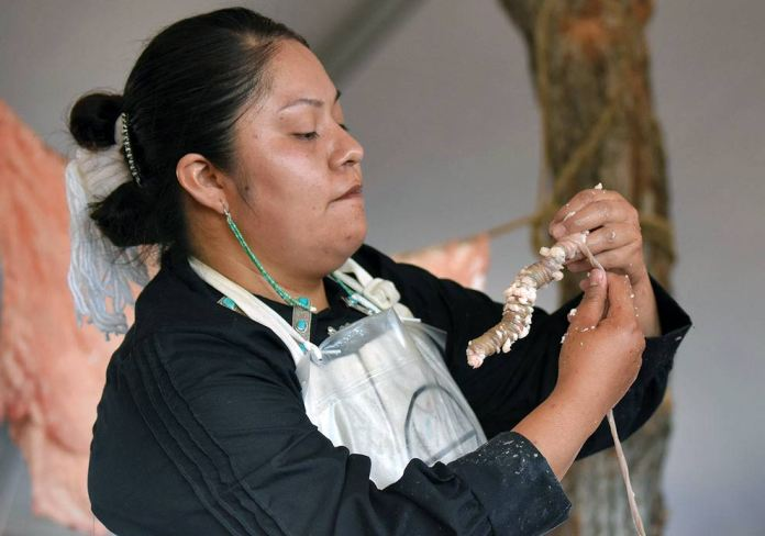Navajo Times   Ravonelle Yazzie Miss Navajo Nation contestant Shaandiin Parrish shows the audience the ach'íí' she prepared at the butchering competition on Monday in Window Rock.