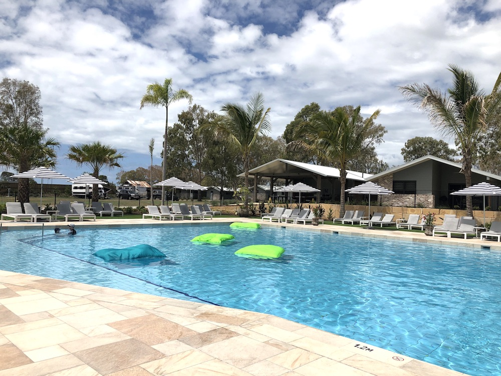 Sandstone Point Holiday Park heated pool with floating bean bags and deck chairs surrounding it.