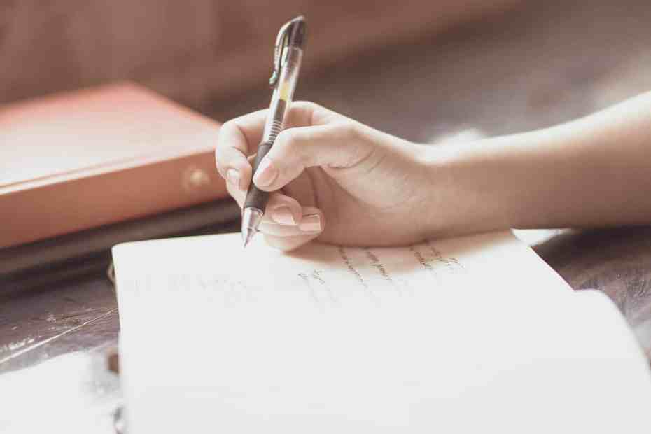 Writer using daily journal prompts to write in their journal