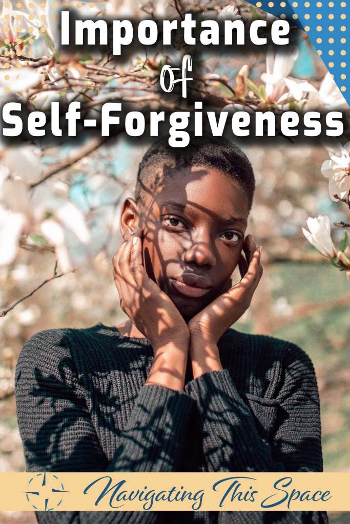 A black woman stands under a white flowers tree, posing with her hands around her face - Importance of self-forgiveness