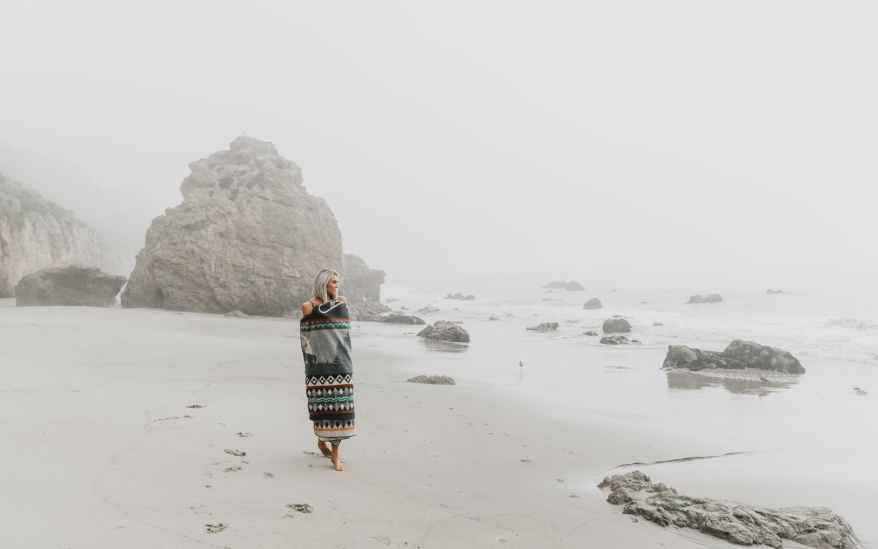 woman wrapped in blanket walking on sandy shore, combat drivers' fatigue