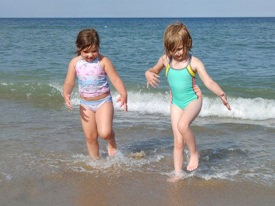 2 girls playing in the ocean. Inspirational family travel quotes.