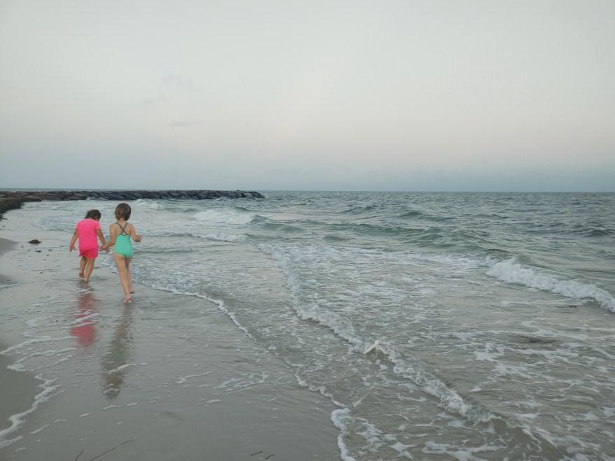 Kids walking on a beach in Cape Cod.