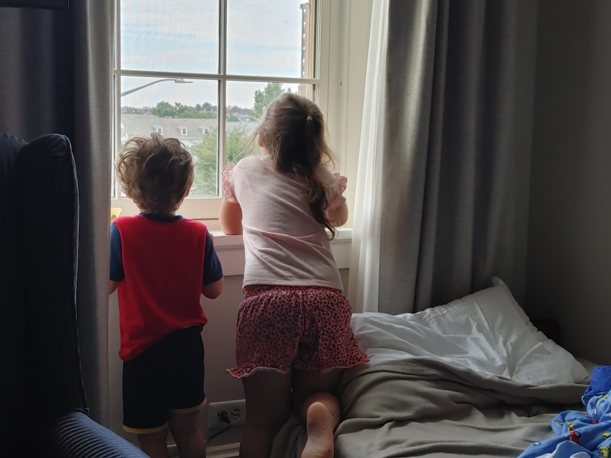 boy and girl looking out a hotel window