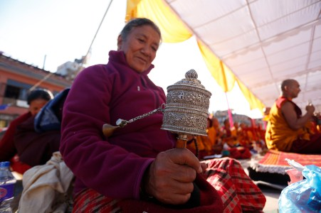 A woman rotates mani during the ritual prayers during the consecration ceremony of the Boudha Stupa in the capital 18 November 2016. The stupa, which has sustained damage to its upper portion in the earthquake in 2015, will formally re-open on 22 November after reconstruction is completed. PHOTO/SANJOG MANANDHAR