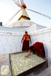 Buddhist monks makes Mandala as they perform ritual prayers during the consecration ceremony of the Boudha Stupa in the capital 18 November 2016. The stupa, which has sustained damage to its upper portion in the earthquake in 2015, will formally re-open on 22 November after reconstruction is completed. PHOTO/SANJOG MANANDHAR