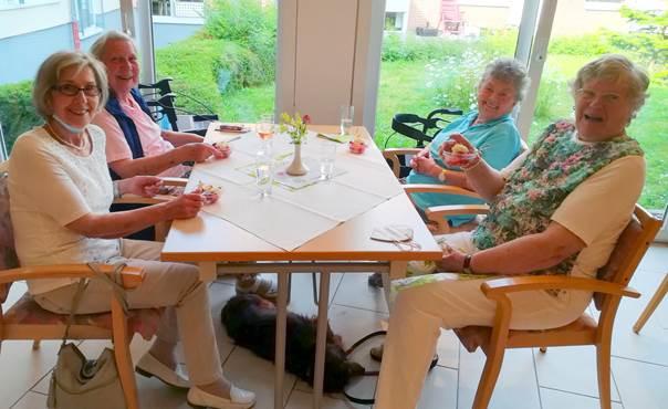 Die Mieterinnen des Betreuten Wohnens an einem Tisch sitzend, Elisabeth Kühn (vorn links), Gisela Wellner (hinten links.), Ursula Husemann (vorne rechts) mit Hundedame Tessa (unterm Tisch) und Annelore Waschul (hinten rechts), freuen sich über das gelungene Spargelessen.