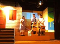 Dorothy speaks to Aunty Em and Uncle Henry about the horrible Miss Gultch. Toto spots something off stage.