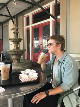 Transfer student Ben Cook sips on some iced coffee before trying a beignet