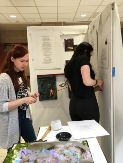 Seniors Kaitlyn Sandvik and Meredith Luchs prepare their art to be displayed during the exhibit.