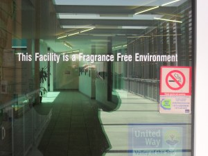 """A glass door has the following text painted in white: This Facility is a Fragrance Free Environment. A """"Thank You for not Smoking"""" cling sticker is posted below the text."""