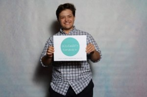 """Oliver Stabbe smiles at the camera while holding a green and white sign that says """"SOLIDARITY: Everybody In"""""""