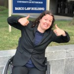 Grace is in formal attire in a wheelchair. She is giving the camera two thumbs up and a big smile. Ze has shoulder-length curly hair that ze is wearing down. In the background is a bright sign for a law building, grass, and stone.