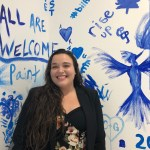 Mercedees stands in front of an artistic wall decorated with blue paintings on a white background. She has long dark hair and is wearing business casual dark clothing. She is smiling in a direction slightly to the left of the camera.