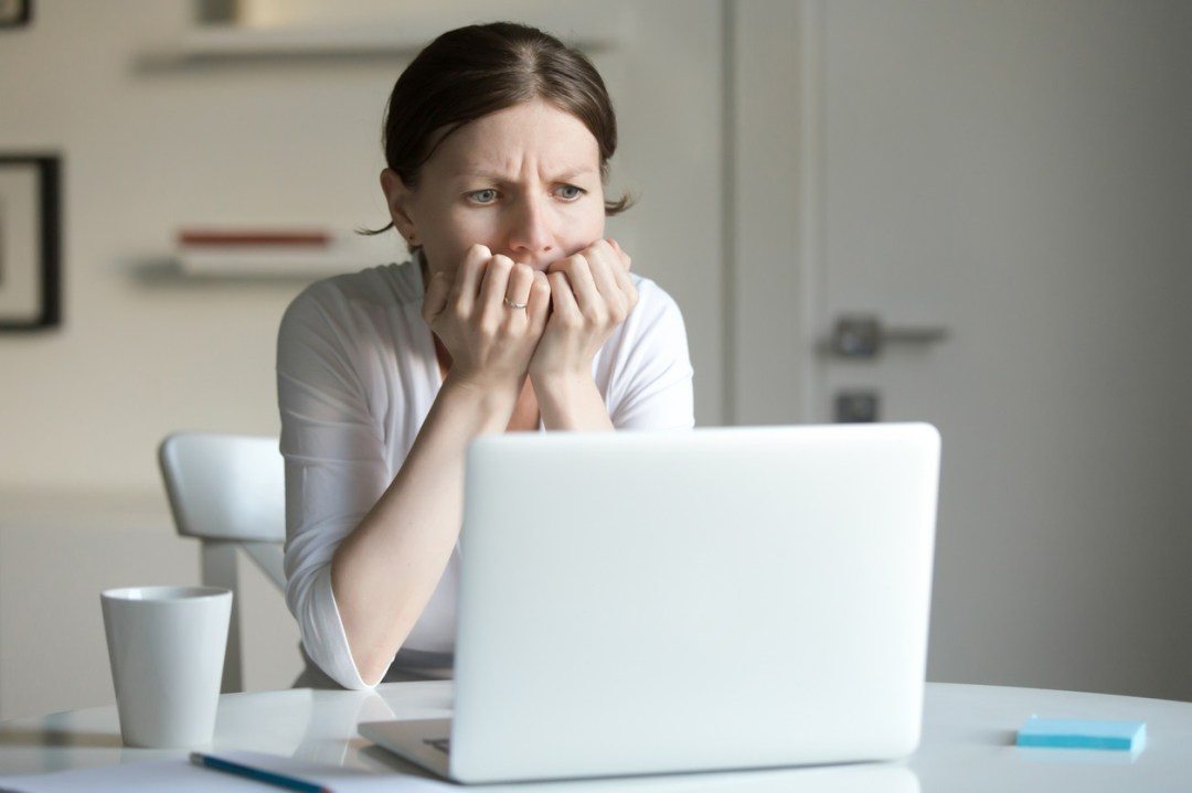 Worried woman looking at laptop