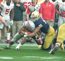 Irish graduate student linebacker Jarrett Grace wraps up Buckeyes junior running back Ezekiel Elliott during Notre Dame's loss to Ohio State on Friday. Grace entered the game after junior Jaylon Smith and freshman Te'von Coney both suffered injuries and finished with nine tackles.
