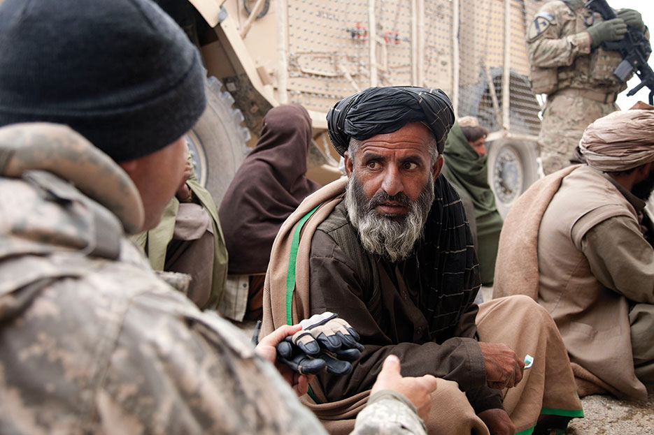 Human Terrain System member speaks with Afghan during Key Leader Engagement in Kandahar Province to discourage locals from hiding contraband for Taliban (DOD/Crystal Davis)