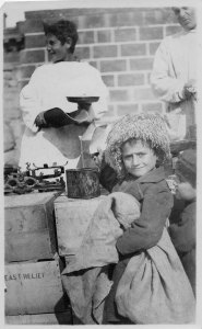 A photograph of a refugee boy with a hat receiving food.