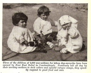 An article with the description of the supplies that are sent to the serve orphans in the nurseries of the Near East Relief. The photo in the article is of three toddlers that are left in the nurseries while their widowed mothers were working.