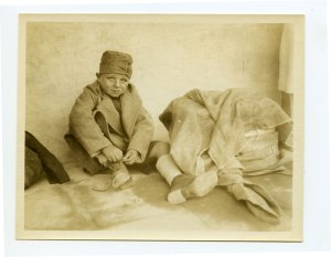 A small boy tying his shoe, wearing a coat and a hat and his eyes are looking up.